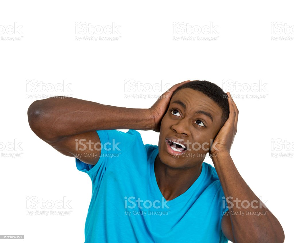 young angry mad unhappy stressed man covering his ears looking up, to say stop making loud noise stock photo