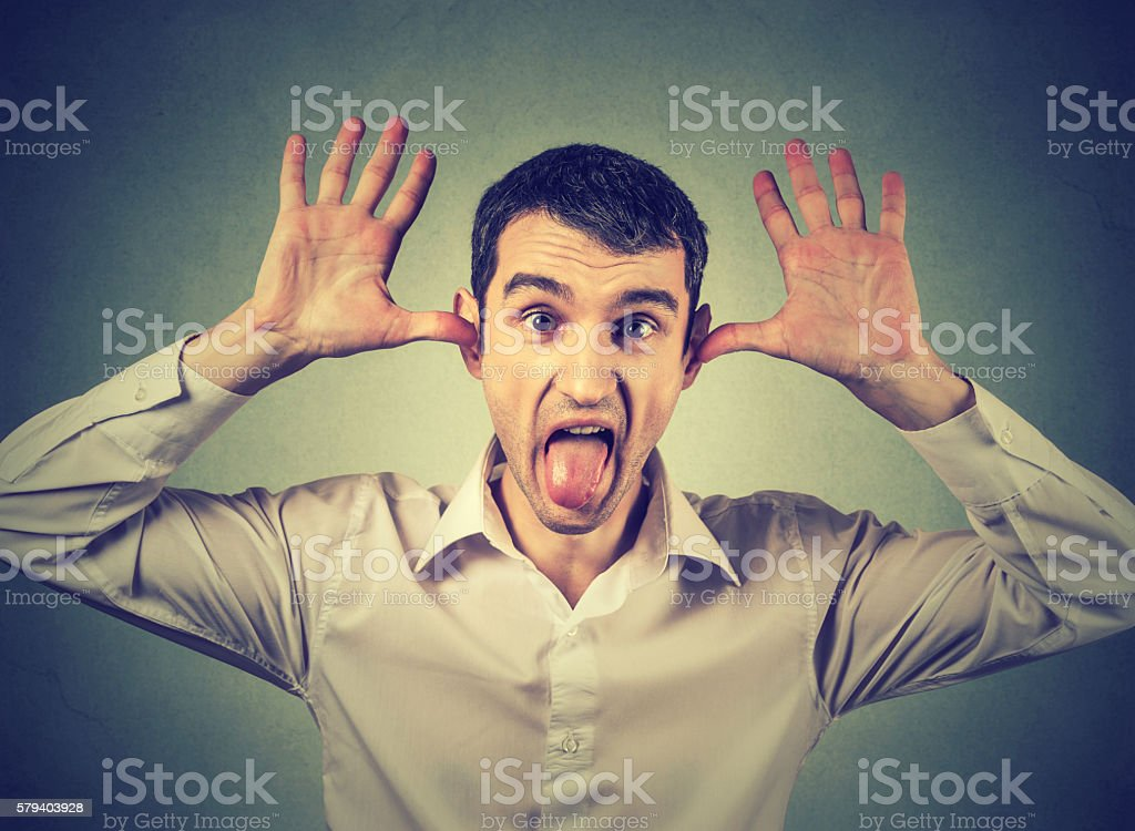 Young angry man, sticking out tongue at you stock photo