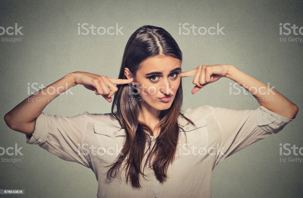 young angry unhappy woman with closed ears looking at you annoyed by loud noise giving her headache ignoring stock photo