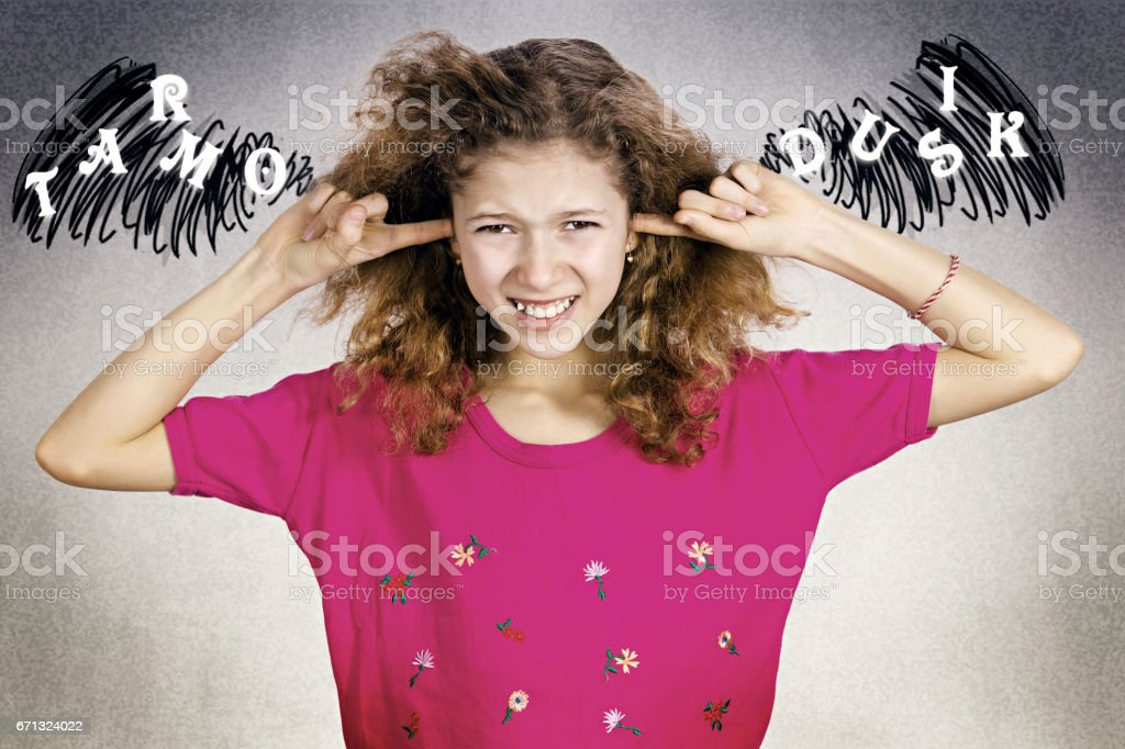 young annoyed, unhappy, stressed girl covering her ears, looking upset stock photo