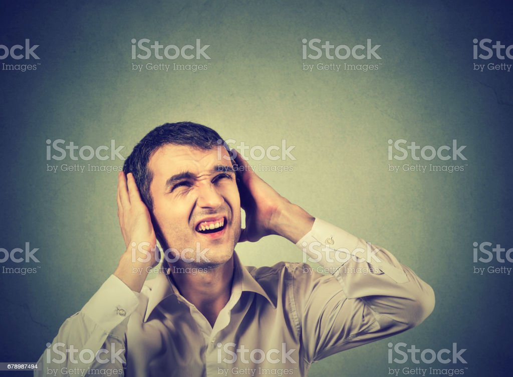 Young annoyed, unhappy, stressed man covering his ears, looking up, stop making loud noise, giving me headache stock photo