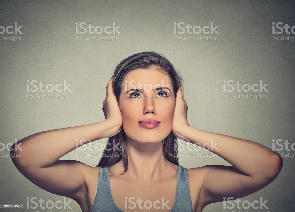 young annoyed, unhappy, stressed woman covering her ears, stock photo
