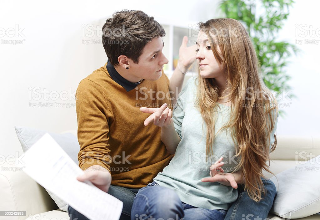 Young anxious couple quarrels by consulting their bank account royalty-free stock photo
