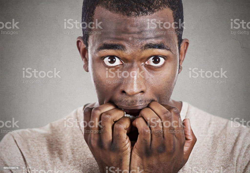 young anxious man biting fingernails looking at you camera stock photo