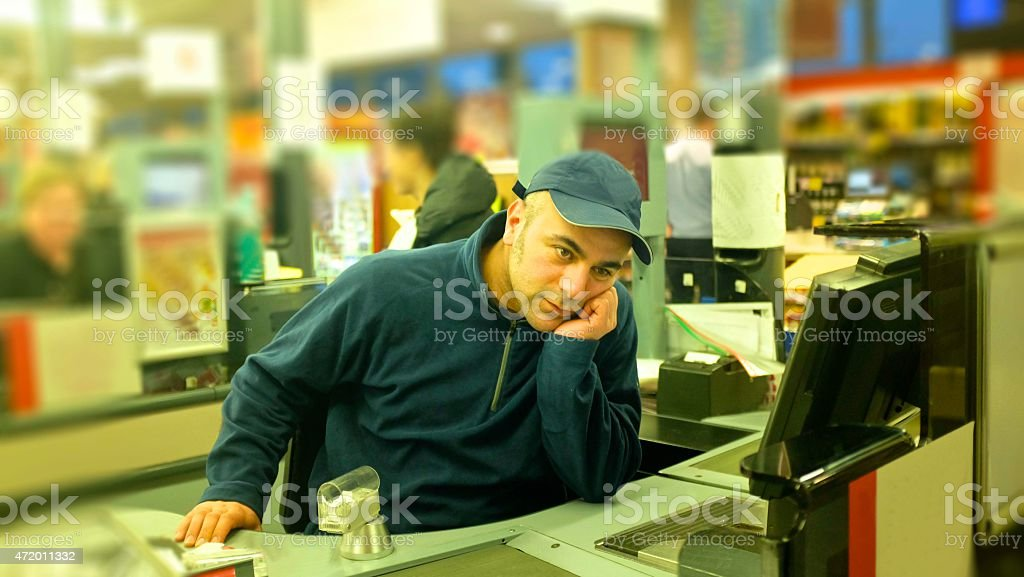 young apprentice cashier at the supermarket part time bored thoughtful stock photo
