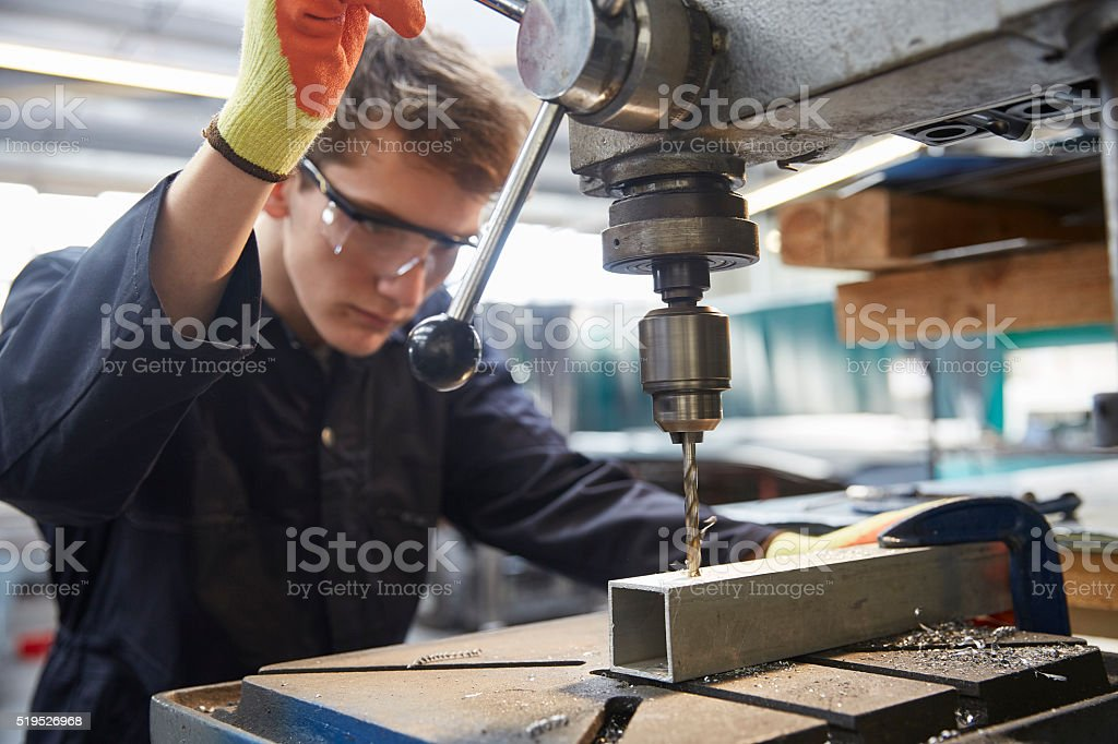 Young apprentice using pillar drill in steel fabrication factory stock photo