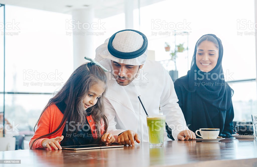 Young Arab family enjoying with tablet pc at cafe stock photo