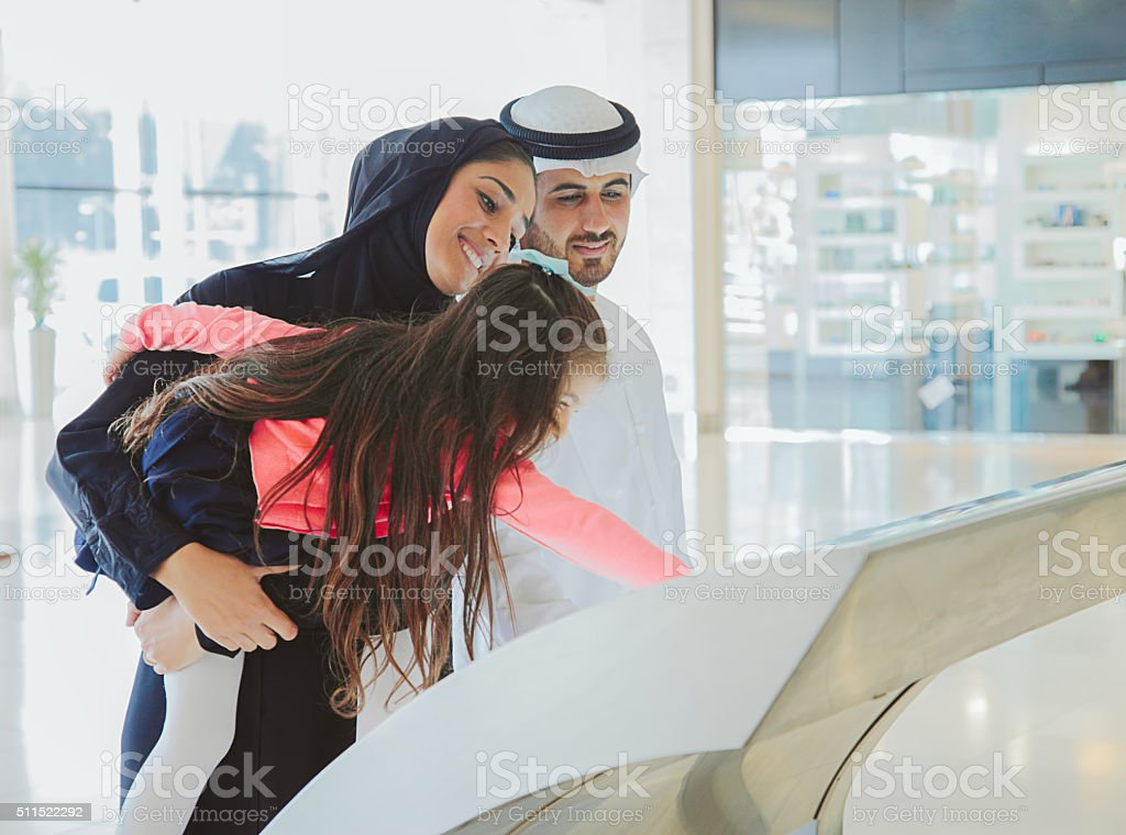 Young Arab family using information display at mall stock photo