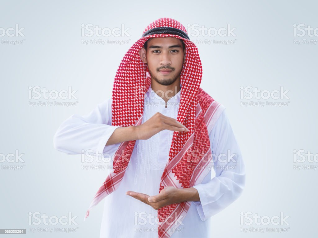 Young arab man with open hands as if holding something, clipping path. Protective, assurance, insurance, care concepts. stock photo