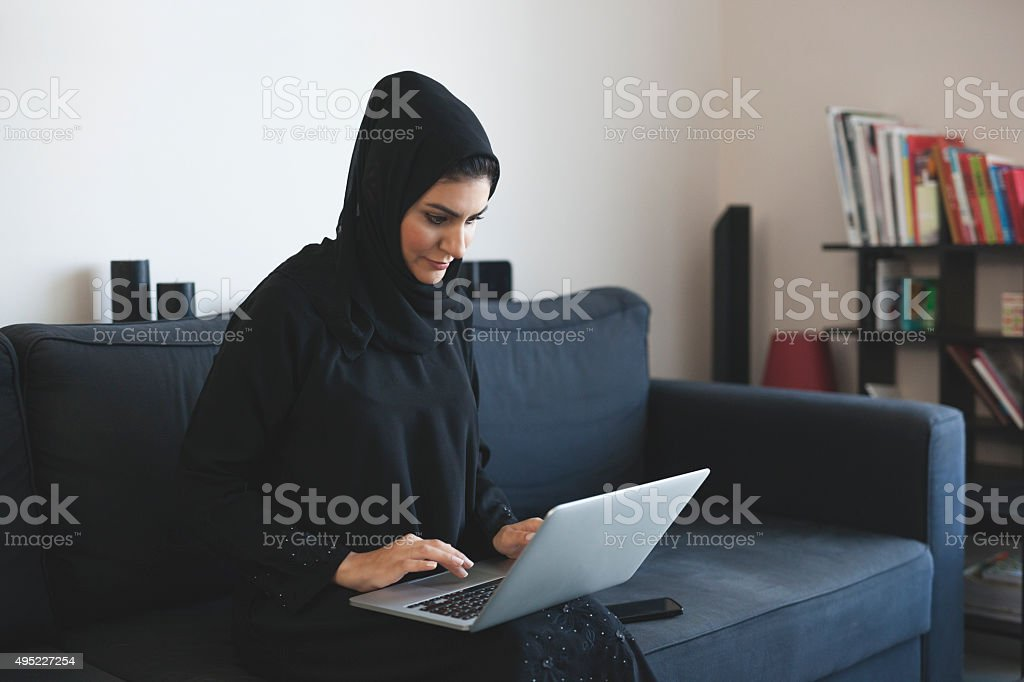 Young Arab Woman Doing Business Using Laptop stock photo