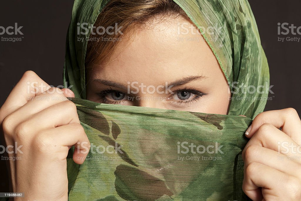 Young arab woman with veil showing her eyes on dark royalty-free stock photo