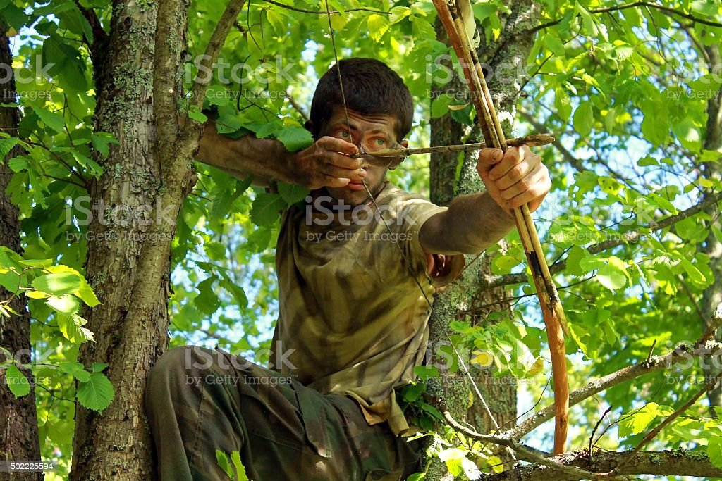 Young archer on the tree stock photo