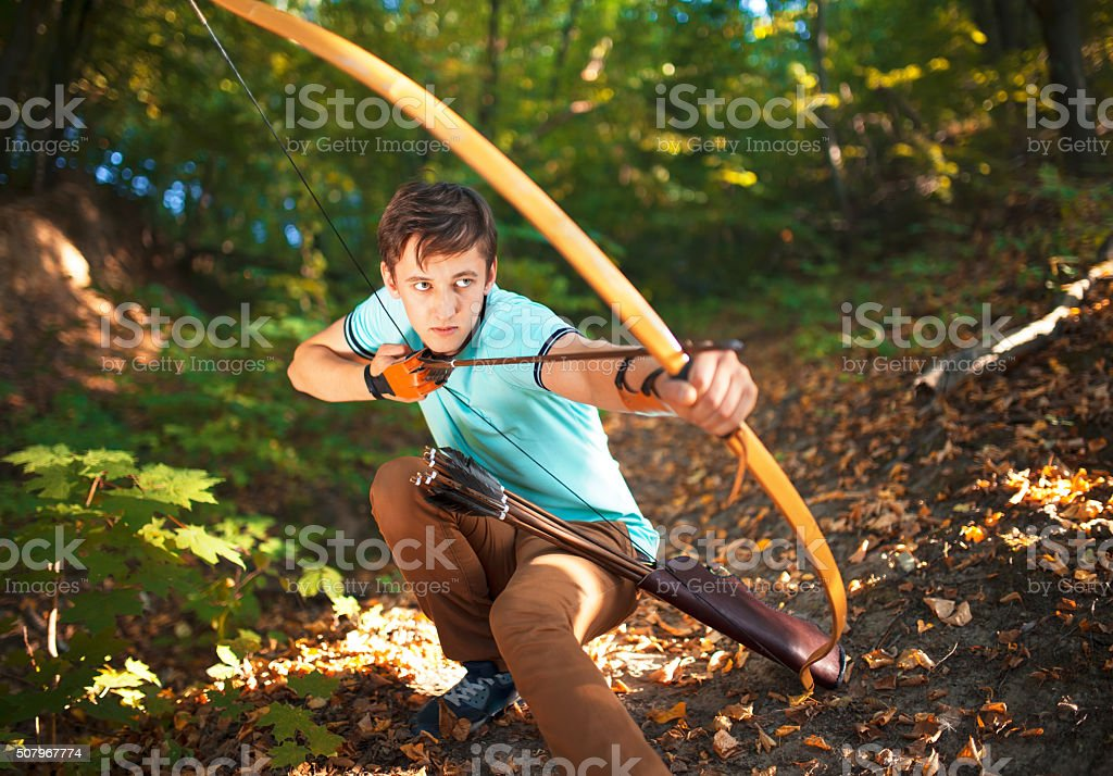 Young archer on training in forest. stock photo