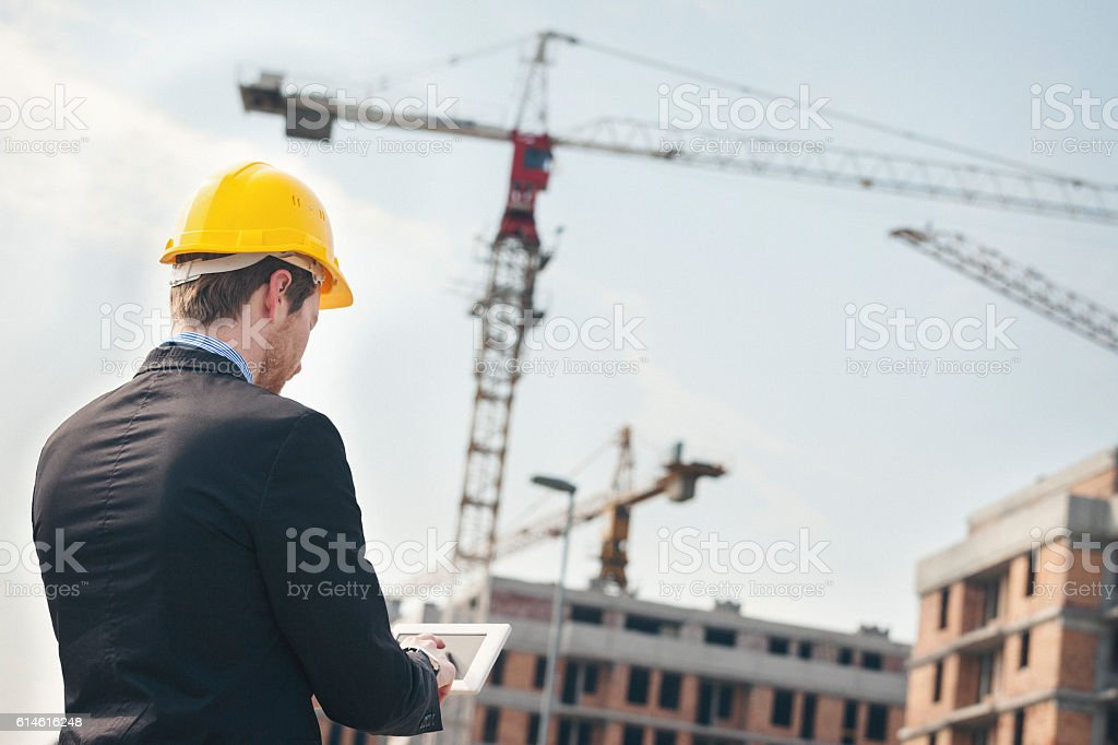 Young architect at construction site using tablet pc stock photo