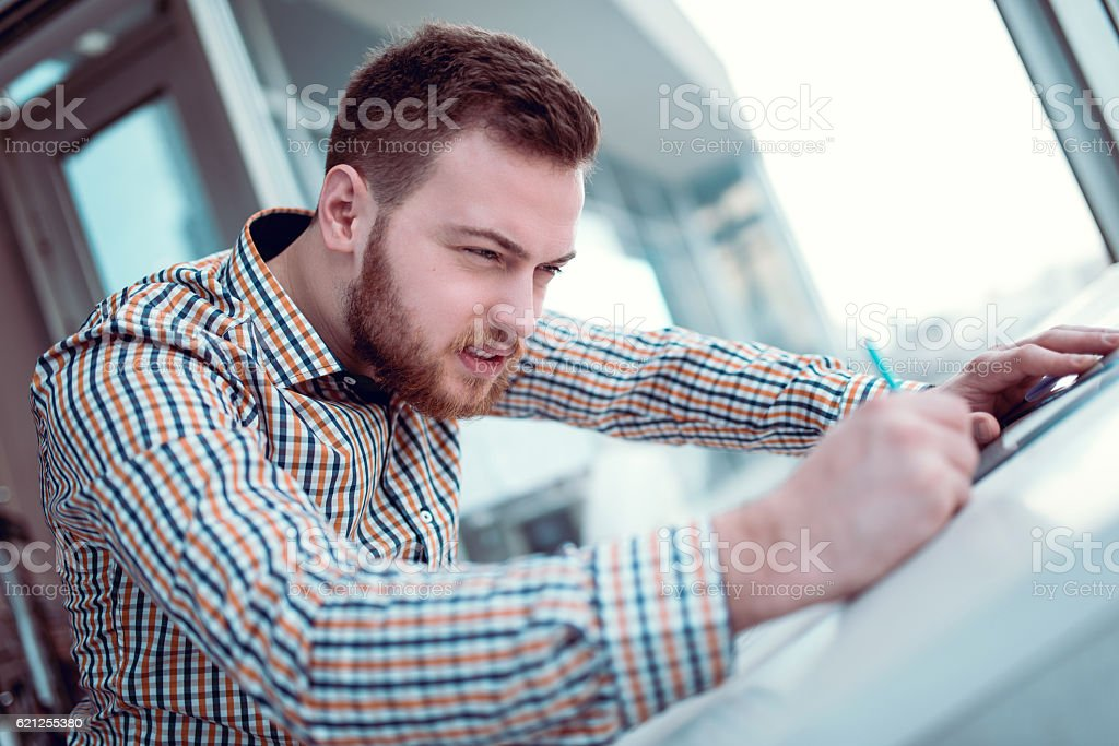 Young Architect Designer Working Blueprint Plans in His Office stock photo