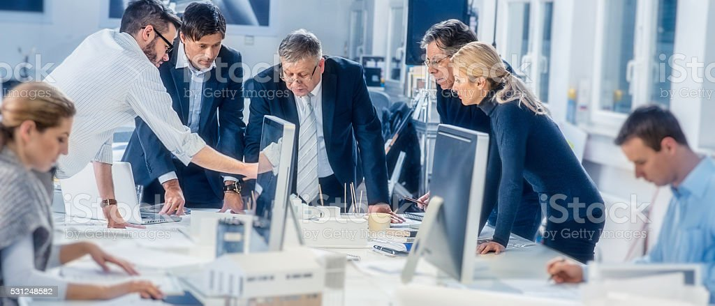 Young architect explaining project plan to clients stock photo