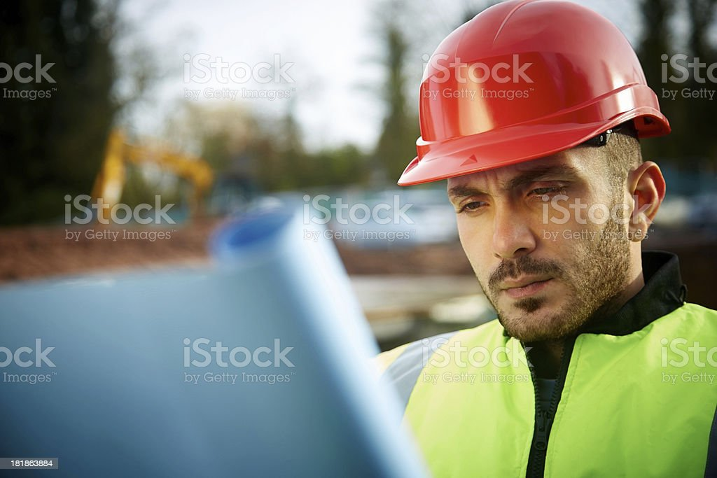 Young architect worker looking at blueprints royalty-free stock photo