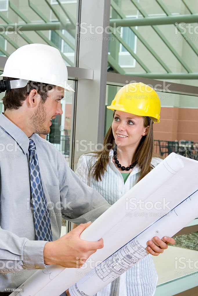 Young Architects Discussing Blueprints royalty-free stock photo
