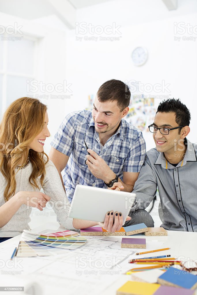 Young Architects review blueprints at office. stock photo