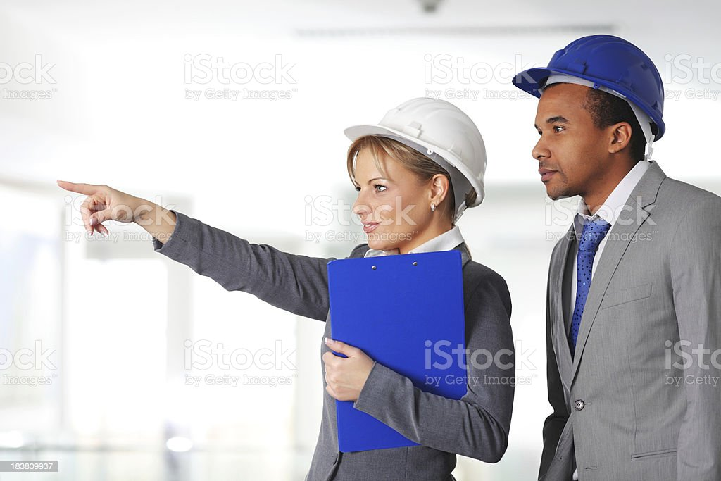 Young architects working together, woman showing with finger. royalty-free stock photo