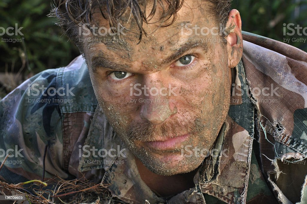 Young army man covered in dirt stock photo