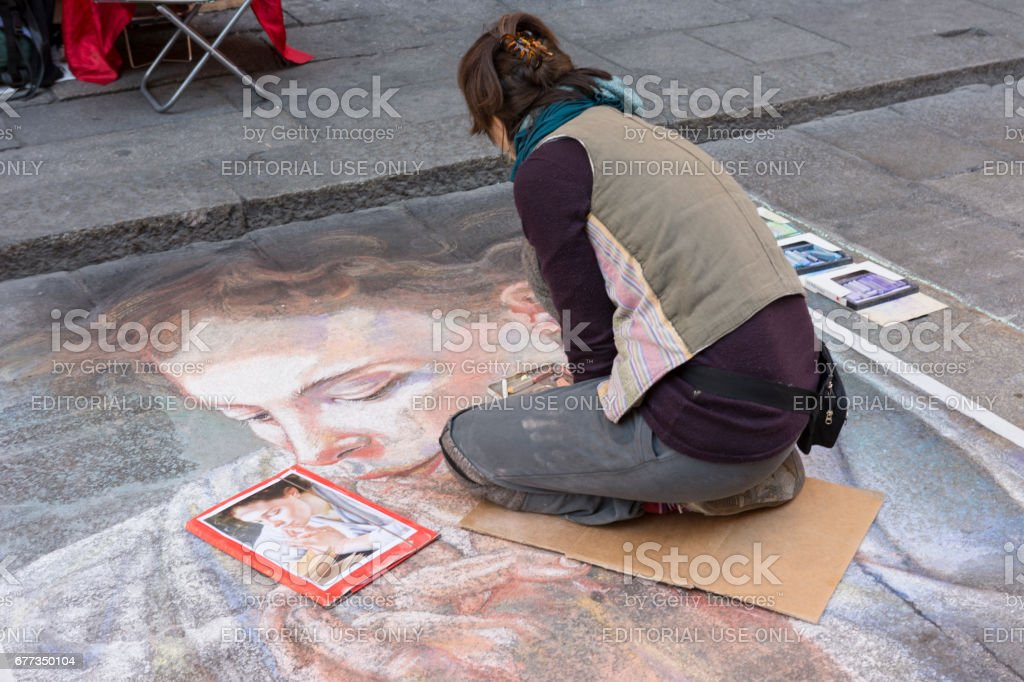 A young artist drawing on the street in Bologna stock photo