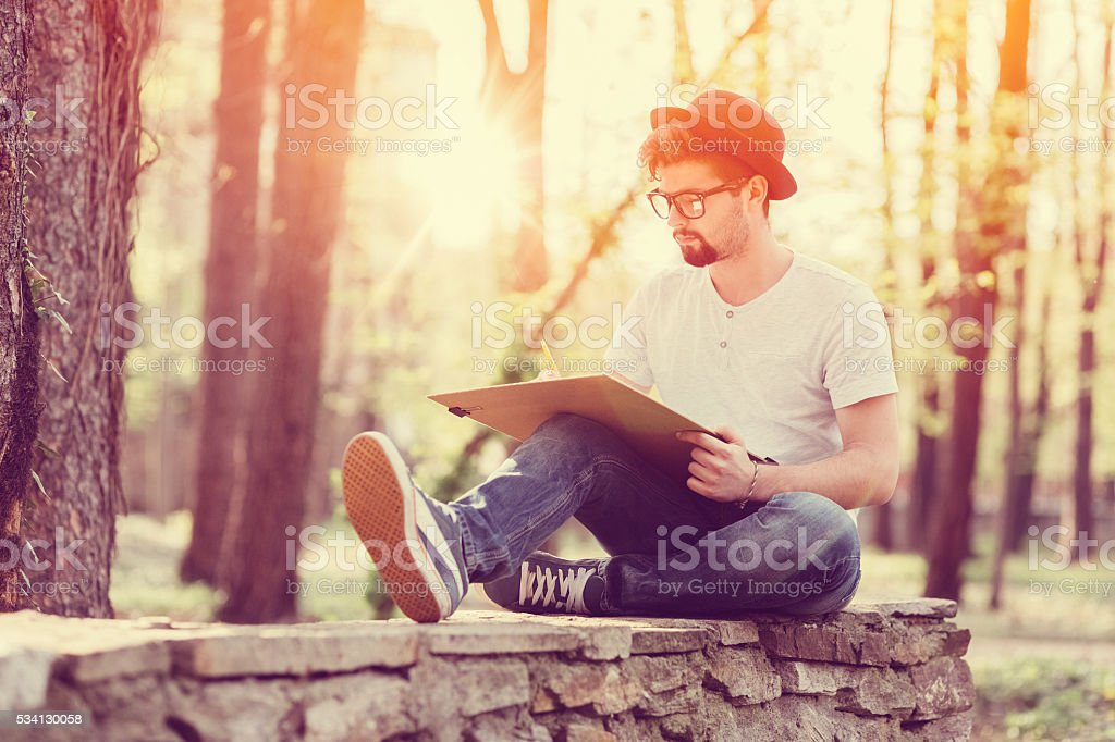 Young artist drawing outside stock photo