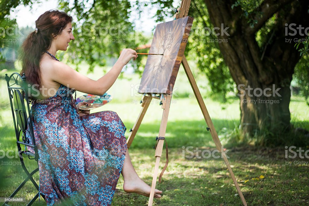 Young artist painting outside stock photo
