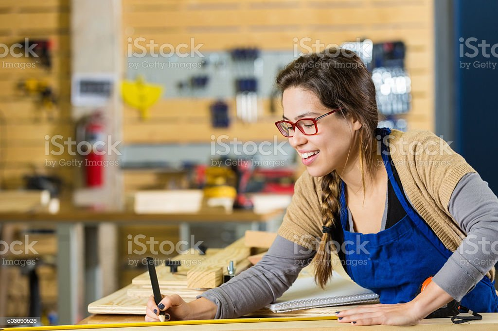 Young artist smiling while creating something with wood in makerspace stock photo
