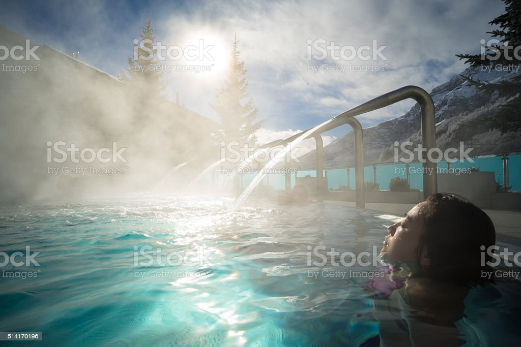 Young Asia woman enjoy hot spring under sunshine stock photo