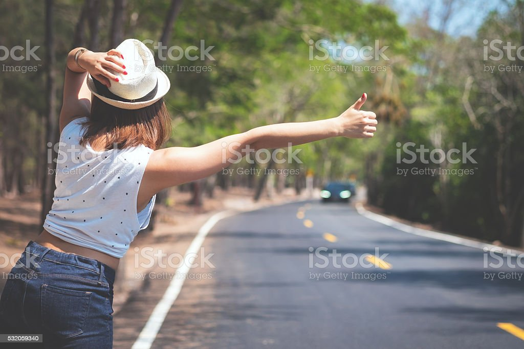 Young Asia woman hitchhiking on the road. stock photo