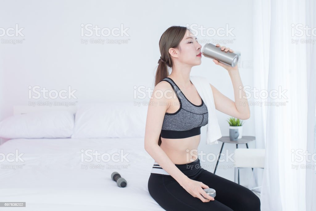 Young asian beautiful fitness girl drinking bottle of water after workout stock photo