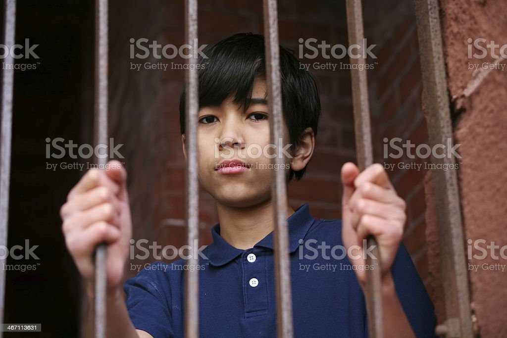 Young Asian boy behind bars, wary expression stock photo