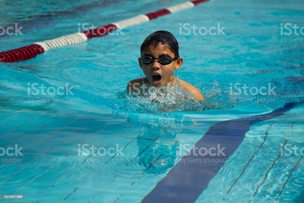 Young asian boy swims breaststroke stock photo