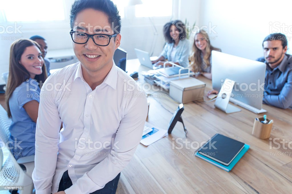 Young Asian business manager standing in front of his team. stock photo