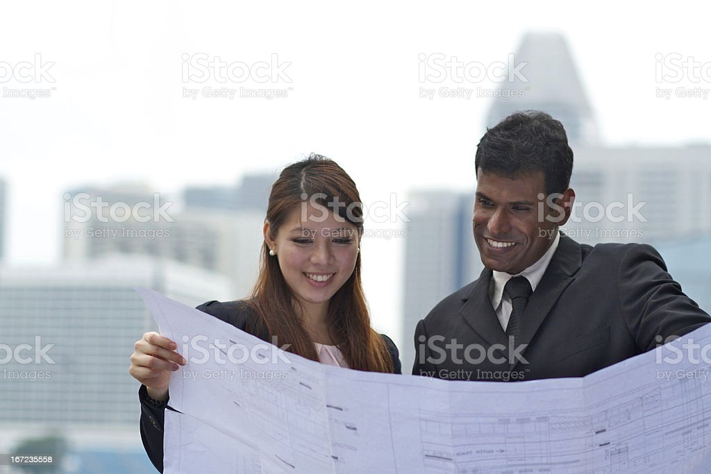 Young Asian Business team discussing blueprints royalty-free stock photo