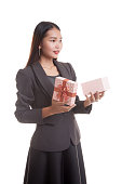 Young Asian business woman open a gift box.