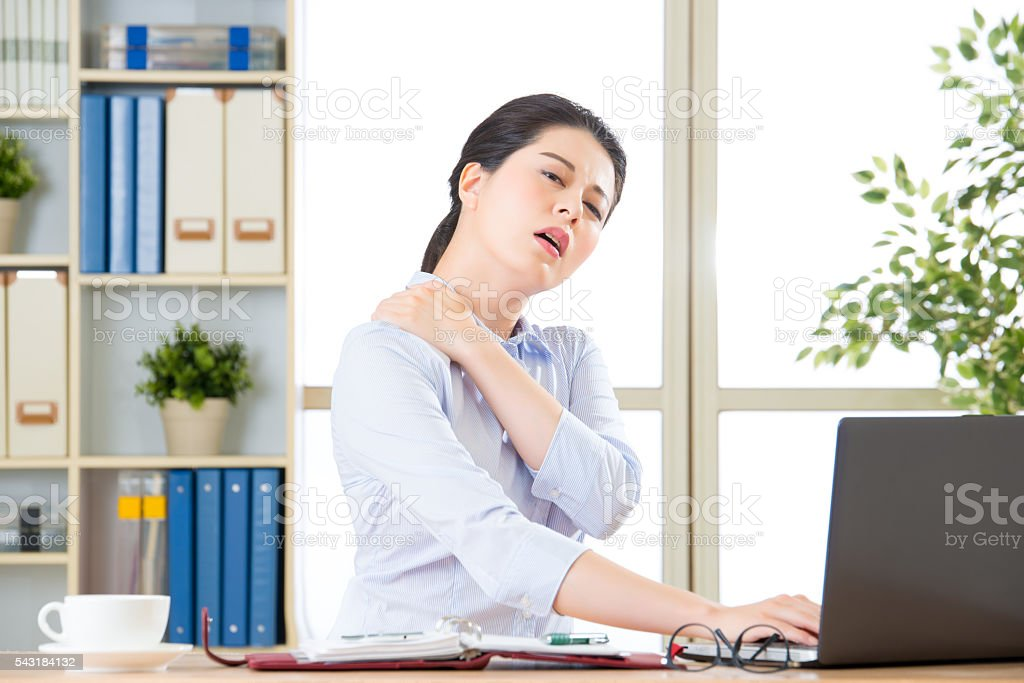 Young asian business woman with pain in shoulders stock photo