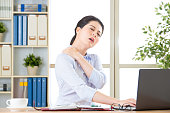 Young asian business woman with pain in shoulders