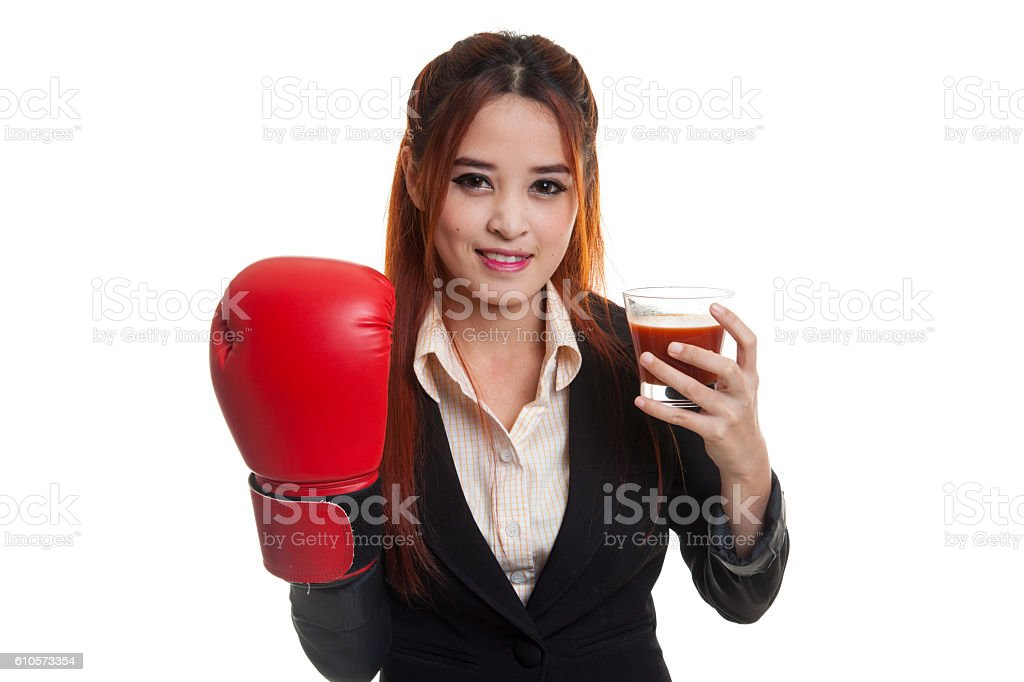 Young Asian business woman with tomato juice and boxing glove. stock photo