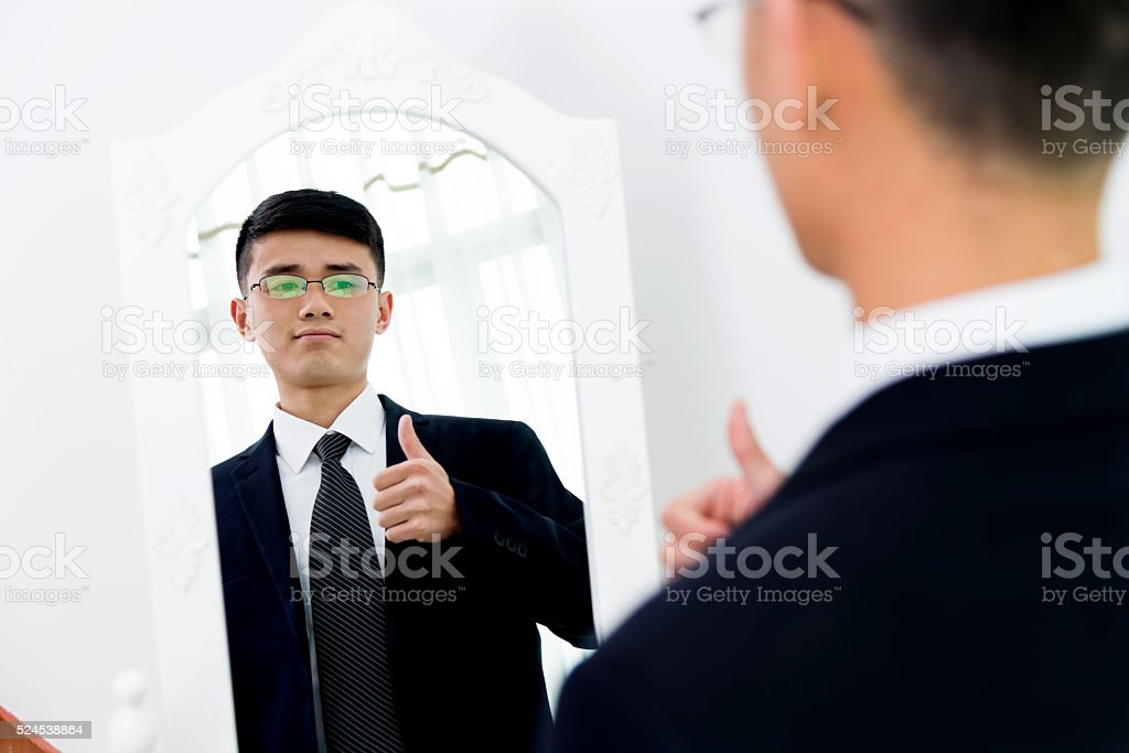 Young asian businessman checking his looks stock photo