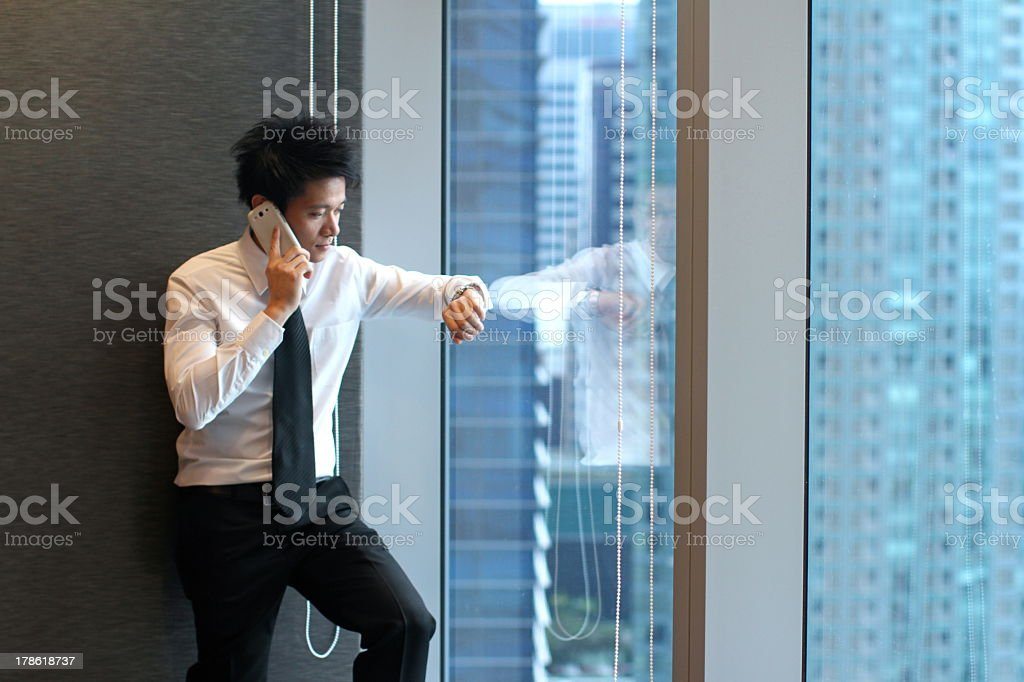 Young Asian businessman checking time on his watch royalty-free stock photo