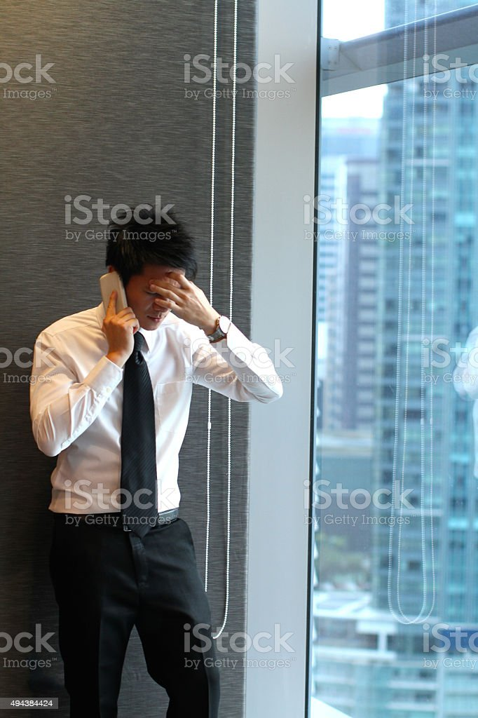 Young Asian Businessman hearing bad news with mobile phone stock photo