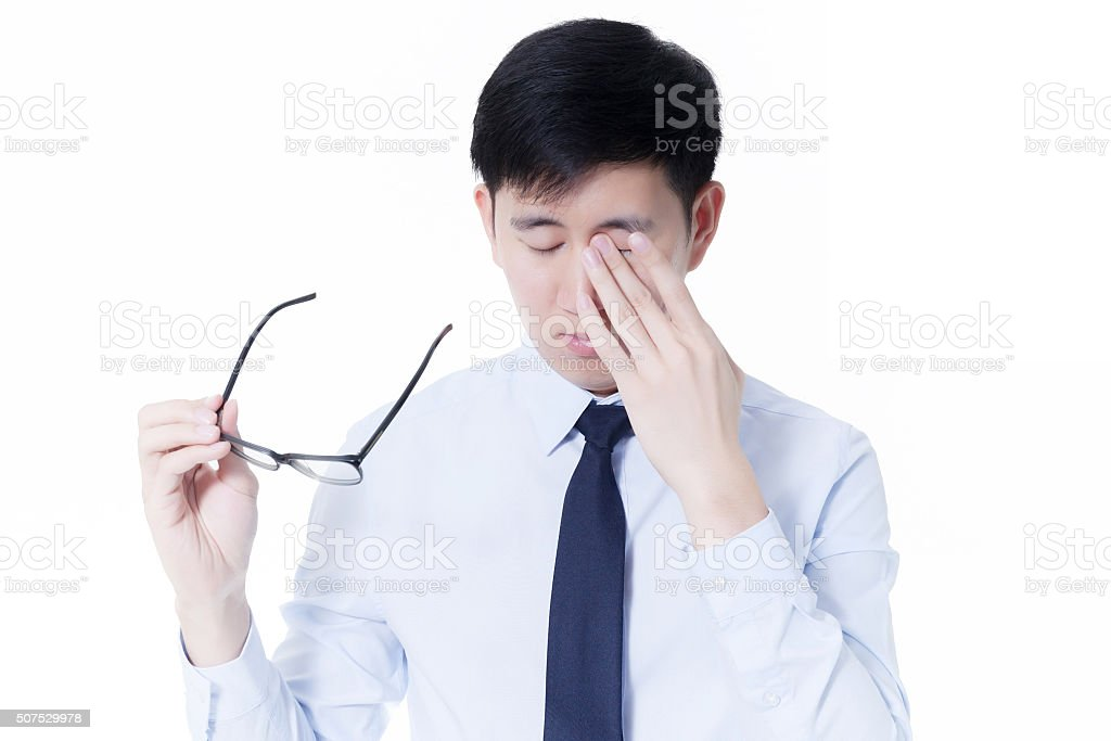 Young Asian businessman rubbing his tired eyes stock photo