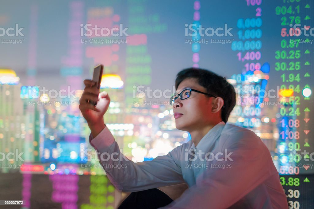 Young Asian Businessman thinking about investing at the office stock photo
