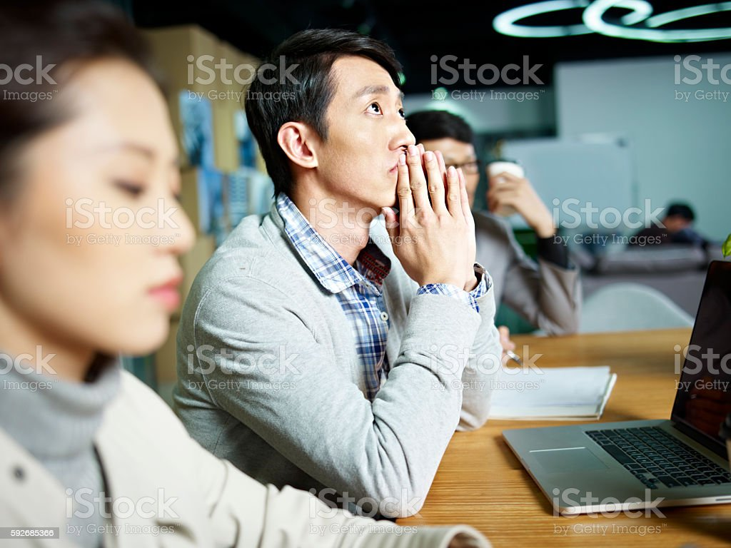young asian businessman thinking during meeting stock photo