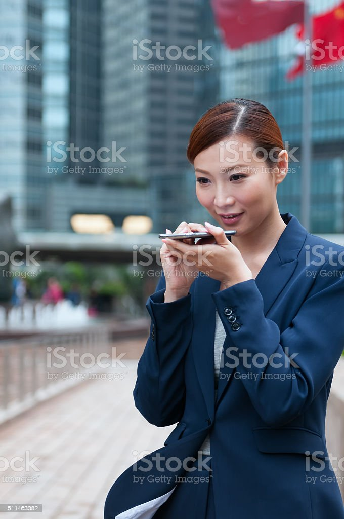 Young Asian Businesswoman Speaking into Smartphone, Hong Kong Financial District stock photo