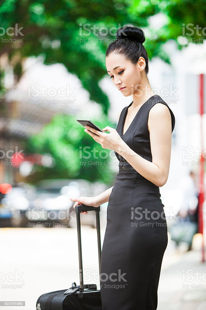 Young Asian Businesswoman Waiting For Her Carpool To Airport stock photo