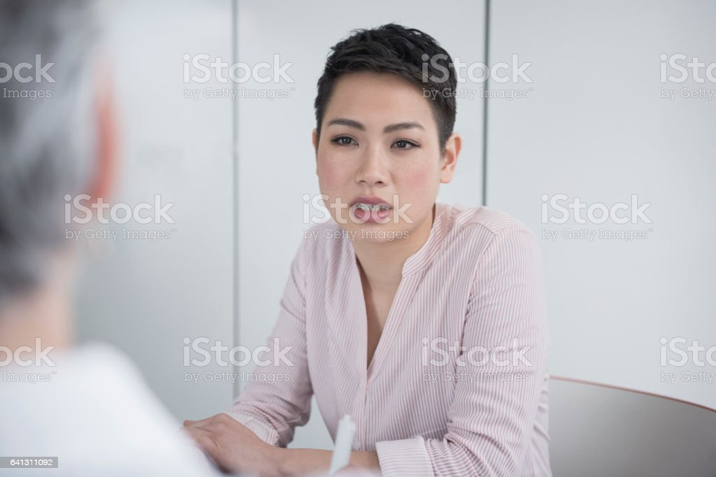 Young Asian businesswoman with short hair listening to colleague stock photo