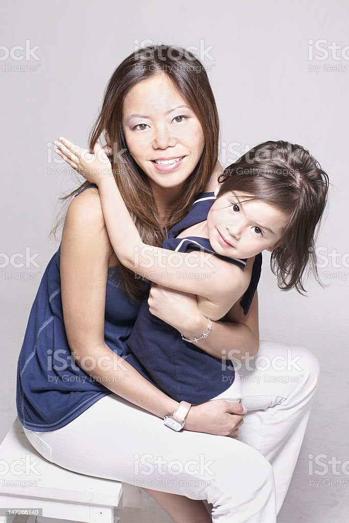 Young Asian Chinese mother playing with Eurasian daughter stock photo